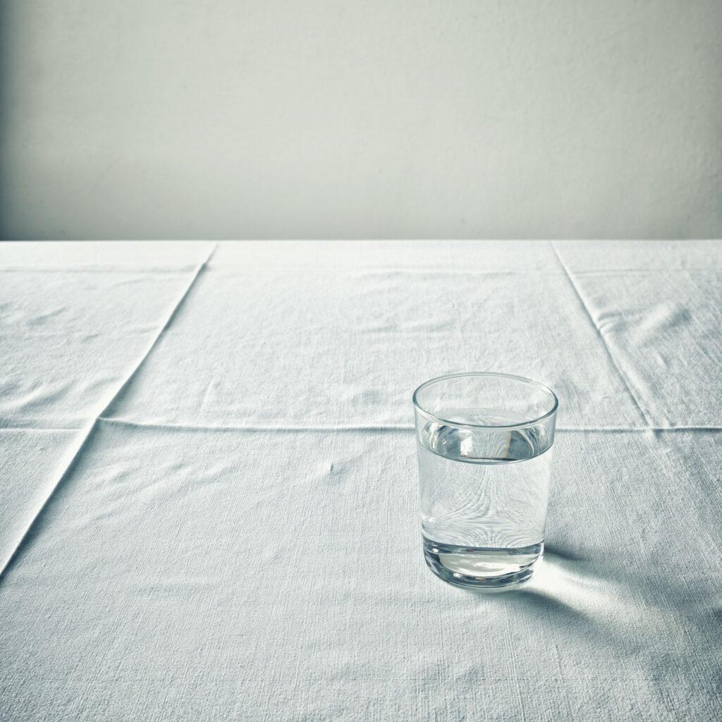 Andreas Huber, Wasserglas auf Leinentischdecke weiß